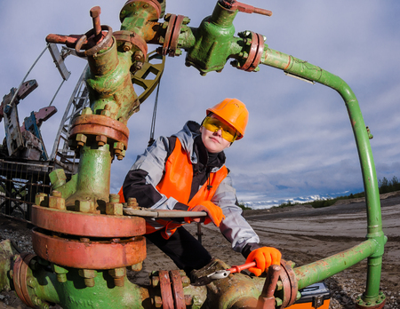 Woman engineer in the oilfield repairing wellhead with the wrench wearing orange helmet and work clothes. Oil rig background. Oil and gas concept. Fish eye shot.