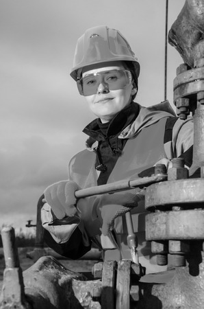 wellhead: Woman engineer in the oil field repairing wellhead with the wrench wearing orange helmet and work clothes. Oil and gas concept. Black and white.