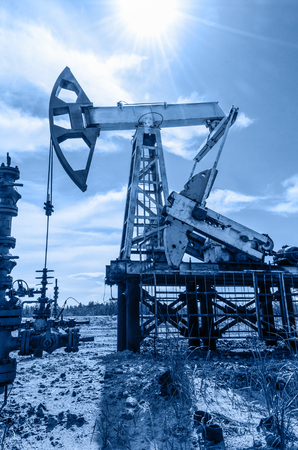 Pump jack and wellhead in the oil field. Oil and gas concept. Toned.
