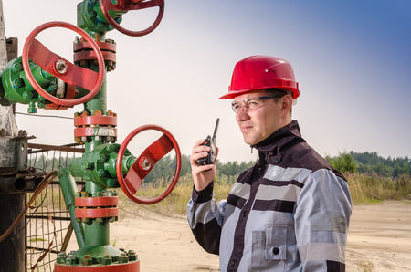 casco rojo: Aceite trabajador de campo cerca de la válvula de cabeza de pozo, usando casco de color rojo y la ropa que hablan en la radio trabajar. Concepto del petróleo y el gas. Foto de archivo