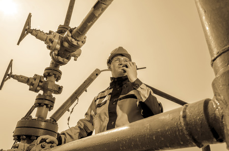 wellhead: Oilfield worker near wellhead valve, wearing helmet and work clothes talking on the radio. Oil and gas concept. Toned.