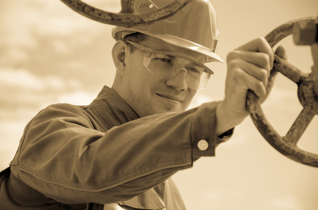 well head: Oilfield worker near blurry well head valve wearing helmet. Oil and gas concept. Toned.