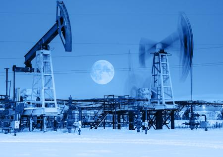 crisis economica: Trabajo gato de bomba de aceite durante la noche. Luna llena. Oilfield durante el invierno. Concepto del petróleo y el gas. Virada.