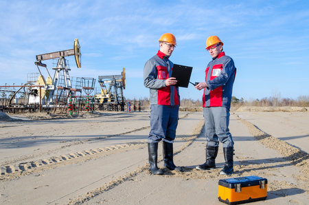 Two workers in the oilfield, one holding the radio second showing papers. Pump jack and wellhead background. Oil and gas concept.