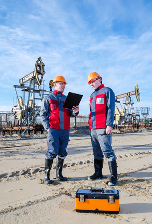 pump jack: Two workers in the oilfield, one holding the radio second showing papers. Pump jack and wellhead background. Oil and gas concept.