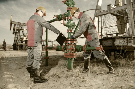wellhead: Workers in the oilfield, one repairing wellhead with the wrench, other supervising. Pump jack and wellhead background. Oil and gas concept. Toned. Stock Photo