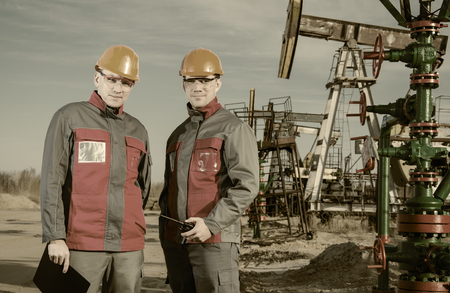 pump jack: Workers in the oilfield, one holding radio in his hand. Pump jack and wellhead background. Oil and gas concept. Toned.