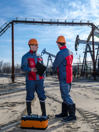 pump jack: Two workers in the oilfield. Pump jack, pipeline and wellhead background. Oil and gas concept.