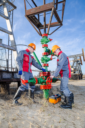 Workers in the oilfield repairing wellhead with the wrench. Pump jack and wellhead background. Oil and gas concept. Stock Photo