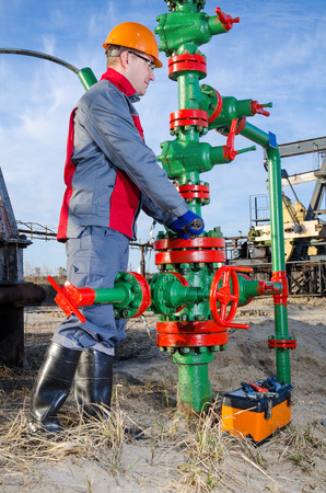 pump jack: Worker in the oilfield repairing wellhead with the wrench. Pump jack background. Oil and gas concept.