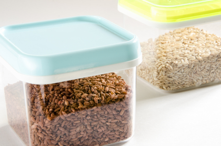 Food storage. Food ingredients (brown rice and wild rice) in plastic containers. Selective focus.  Stock Photo