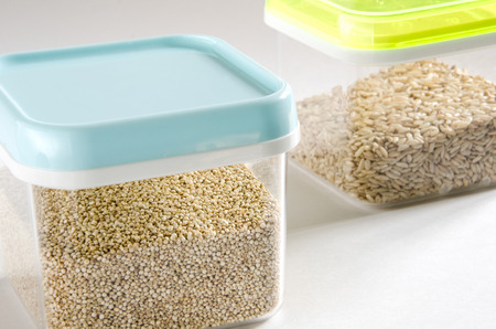 food storage: Food storage. Food ingredients (quinoa and wild rice) in plastic containers. Selective focus. Stock Photo