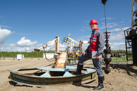 pump jack: Worker near broken pump jack holding radio and tablet computer in the oilfield. Pump jacks and wellhead background. Oil and gas concept. Stock Photo