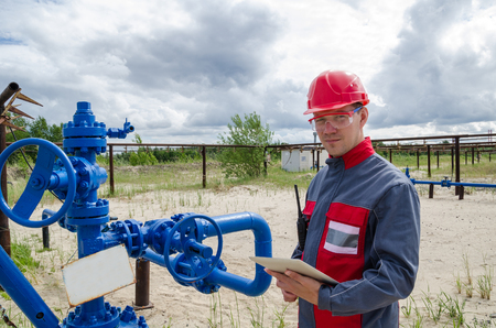 Worker near broken pump jack holding radio and tablet computer in the oilfield. Pipeline background. Oil and gas concept. Stock Photo