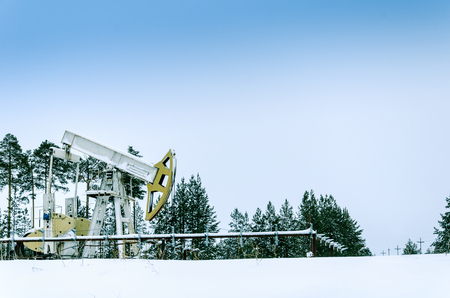 pump jack: Pump jack in the oilfield situated in the beautiful winter forest. Environmental pollution. Oil and gas concept.