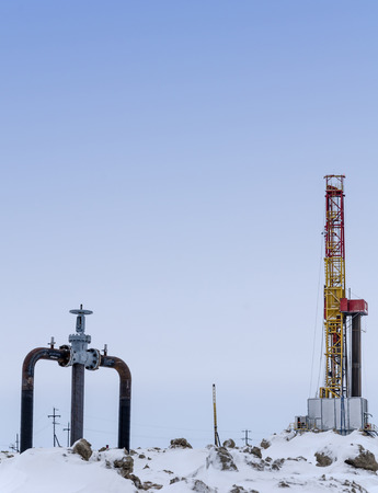 Oil rig and wellhead in the oilfiled during winter time. Oil and gas concept.