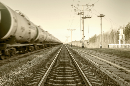 Train with oil tanks moving. Transportation of fuel on the railroad. Motion blur. Toned. Stock Photo