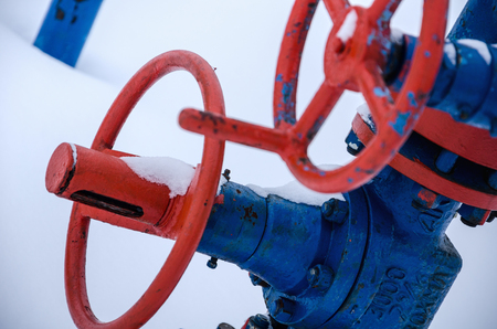 pipework: Wellhead valve. Oil and gas concept. Industrial site during winter period.
