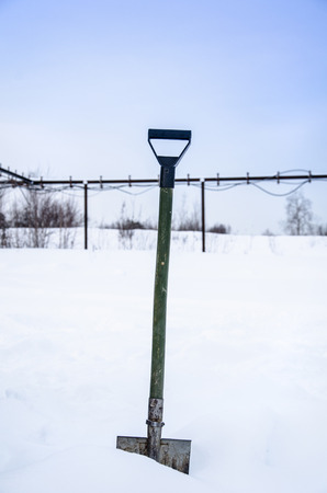 Snow cleaning with the shovel. Industrial site and pipeline background.