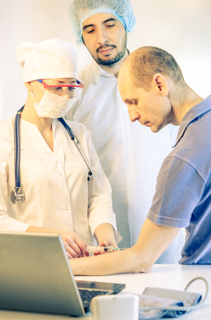 Group portrait of medical doctors in hospital having consultation with patient and making injection. Man wearing surgeon coat and woman wearing white cap. Focus on woman doctor. Toned.