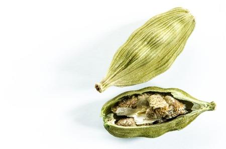 乾燥カルダモンの種子は、白で隔離。コピー スペースと食品の背景。クローズ アップのマクロ撮影します。平面図です。