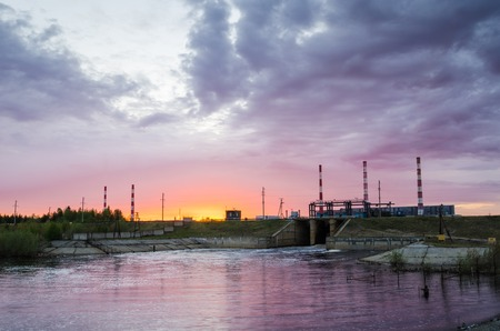 spillway: Gas power plant during sunset. Spillway and lake foreground. Energy industry concept.