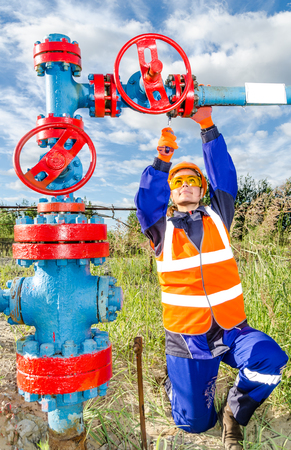 Woman worker in the oilfield repairing wellhead, wearing orange helmet and work clothes. Industrial site background. Oil and gas concept. Stock Photo