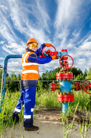power wrench: Woman worker in the oilfield repairing wellhead, wearing orange helmet and work clothes. Industrial site background. Oil and gas concept. Stock Photo
