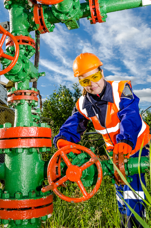 Woman worker in the oilfield repairing wellhead wearing orange helmet and work clothes. Industrial site background. Oil and gas concept. Stock Photo