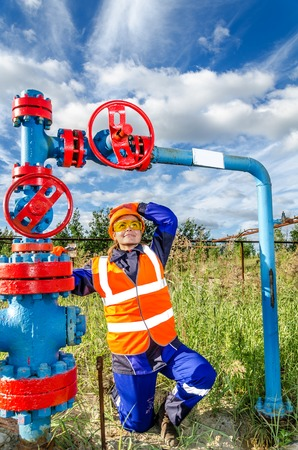 Woman worker in the oilfield near wellhead, wearing orange helmet and work clothes. Industrial site background. Oil and gas concept. Stock Photo
