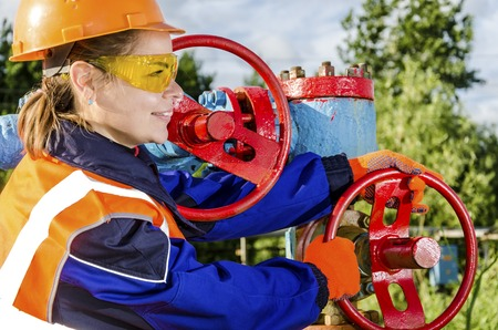 Woman worker in the oilfield repairing wellhead wearing orange helmet and work clothes. Stock Photo