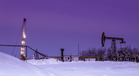 Pump jack, oil rig and pipeline  in the oilfield. Winter period. Oil and gas concept. Toned.