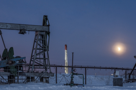 Pump jack, wellhead, pipeline and oil rig during moon eclipse in the oilfield. Winter period. Oil and gas concept. Toned. Stock Photo