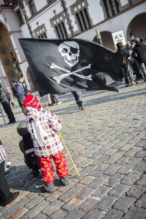 A little boy holding large black pirate flag and waving with it