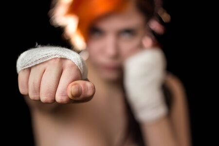 Yound beautiful redhead colored woman posing as kickboxer photo