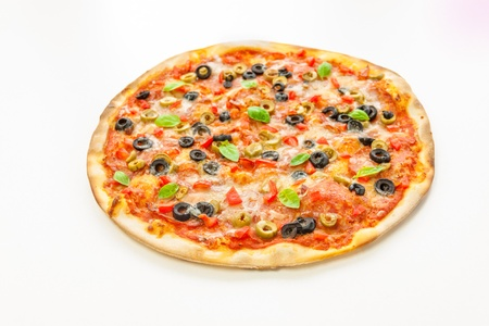 turning table: Beautiful multi colored and crispy pizza with basil, melted cheese and salami slowly turning on rotating table with white background