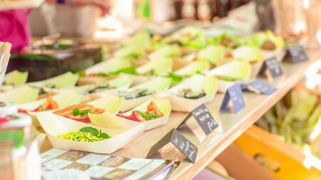A person taking business card from the food stand with prepared raw food dishes Zdjęcie Seryjne