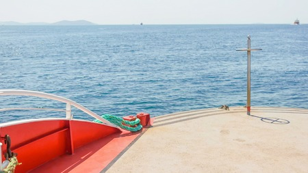 High angled, front view over the red colored deck of the saling boat on the blue ocean with the Island in front