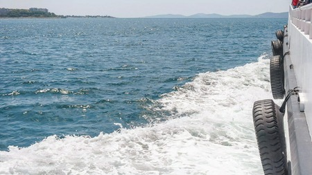 Side view, over the deck of the saling boat on the blue sea with water waves on the side Zdjęcie Seryjne