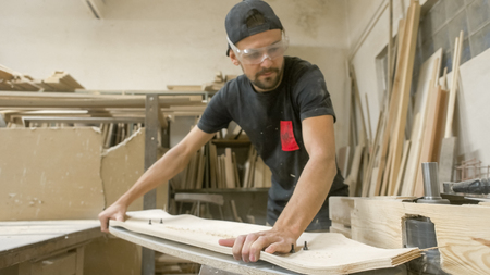Young artisan man cutting longboard deck