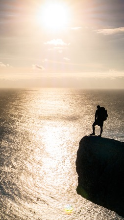 An adult standing on the edge of the cliff above the ocean