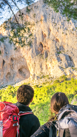 Young adult caucasian couple looking at the mountain wall to climb