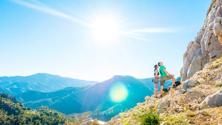 Young adult caucasian couple examining the mountain wall to climb