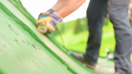 Construction worker using tools to scrape off green paint