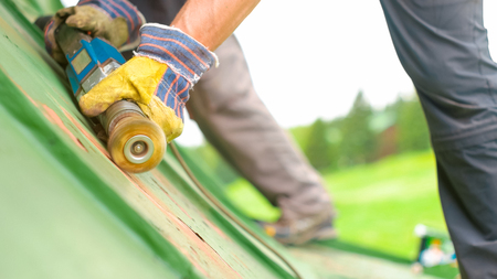 Construction worker using tools to scrape off green paint, slowmotion