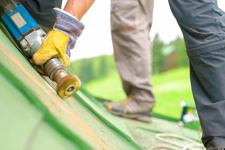 Construction worker using tools to scrape off green paint, low angled