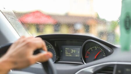 Caucasian man driving a car and placing his hand slowly on the wheel