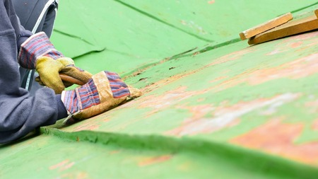 scraping: Worker sitting on the roof and scraping of fading paint