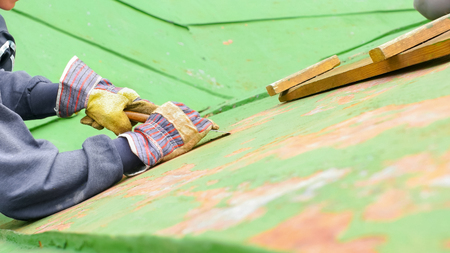 Worker peeling off green paint from the high up roof