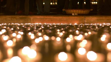 Candles lit by people burning in front of the church podium
